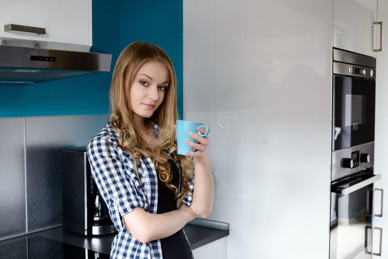 Кофе красивой белокурой женщины выпивая в кухне стоковое фото rf