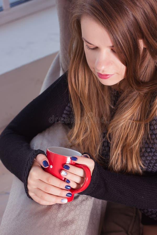 Кофе красивой женщины выпивая сидя окном стоковое изображение