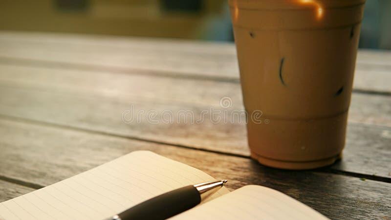 Кофе льда в на вынос чашке с тетрадью и ручка на стороне Bo стоковая фотография