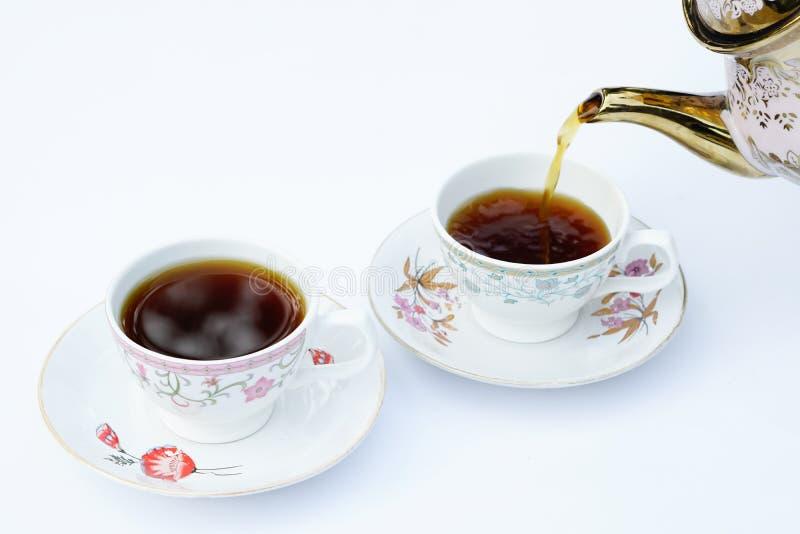 Кофе льет в чашку стоковые изображения