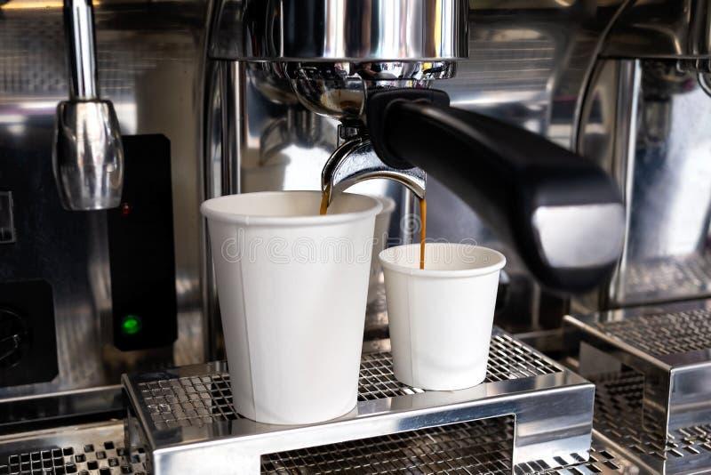 Кофе машины эспрессо лить в 2 бумажного стаканчика стоковое фото rf
