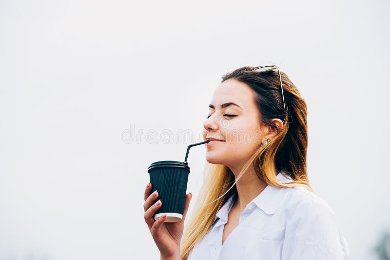 Кофе милой девушки выпивая, усмехаясь, глаза закрыл, космос экземпляра стоковое изображение rf