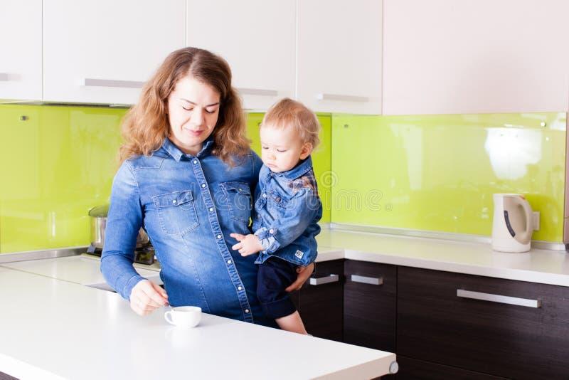 Кофе молодой матери выпивая держа малого мальчика в ее оружиях стоковая фотография