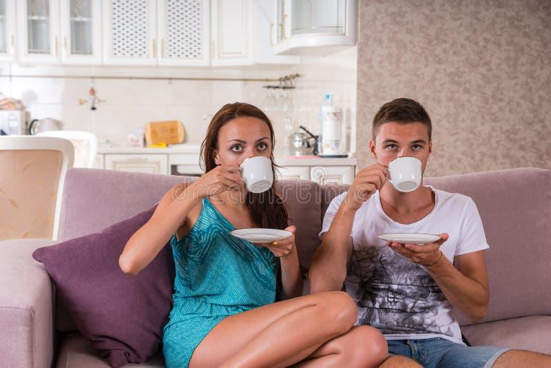Кофе молодых пар выпивая на софе дома стоковая фотография