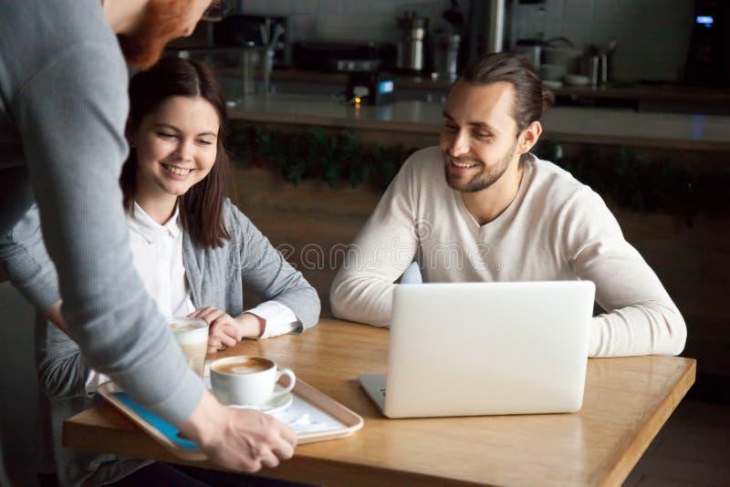 Кофе официанта служа к счастливым тысячелетним парам в кафе стоковая фотография rf