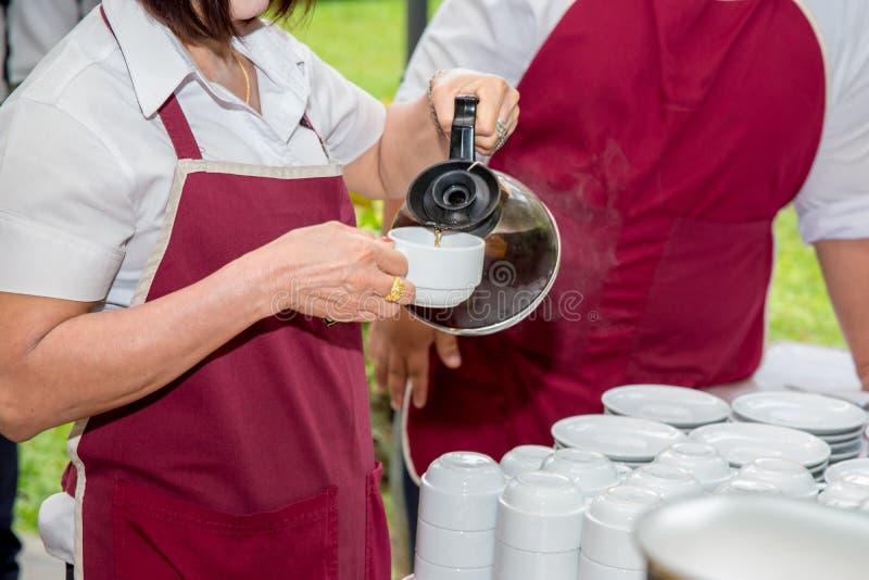 кофе официантки лить в белой чашке для служения к wedding гостю стоковые изображения rf