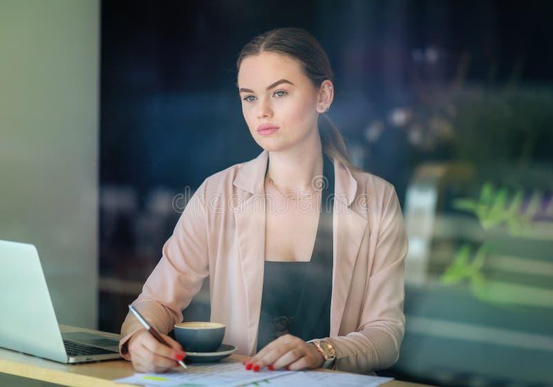 Кофе привлекательной коммерсантки выпивая и работа на ноутбуке перед местным кафем Терраса на тротуаре стоковое изображение