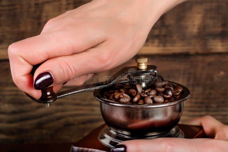 Кофе руки женщины меля зажарил в духовке фасоли в ретро мельнице и деревянной предпосылке стоковая фотография