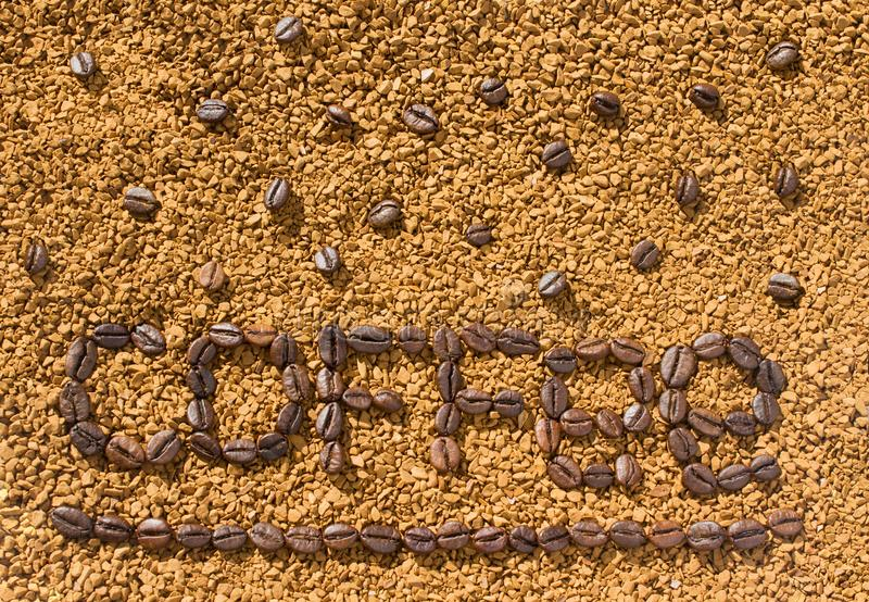 Кофе слова от кофейных зерен на предпосылке разбросанного растворимого кофе стоковое фото rf