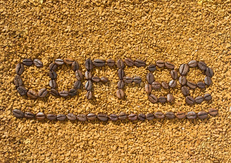 Кофе слова от кофейных зерен на предпосылке разбросанного растворимого кофе стоковое фото