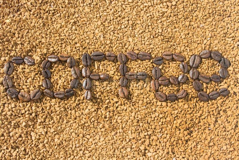 Кофе слова от кофейных зерен на предпосылке разбросанного растворимого кофе E стоковое изображение