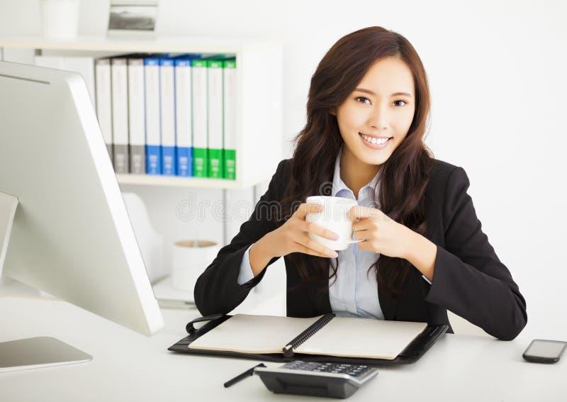 Кофе счастливой молодой коммерсантки выпивая в офисе стоковое изображение