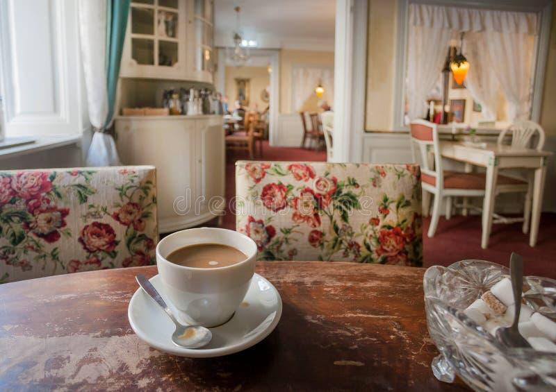 Кофе с молоком на ретро таблице внутри старого ресторана, с винтажной мебелью и уютными комнатами исторического дома стоковые изображения rf