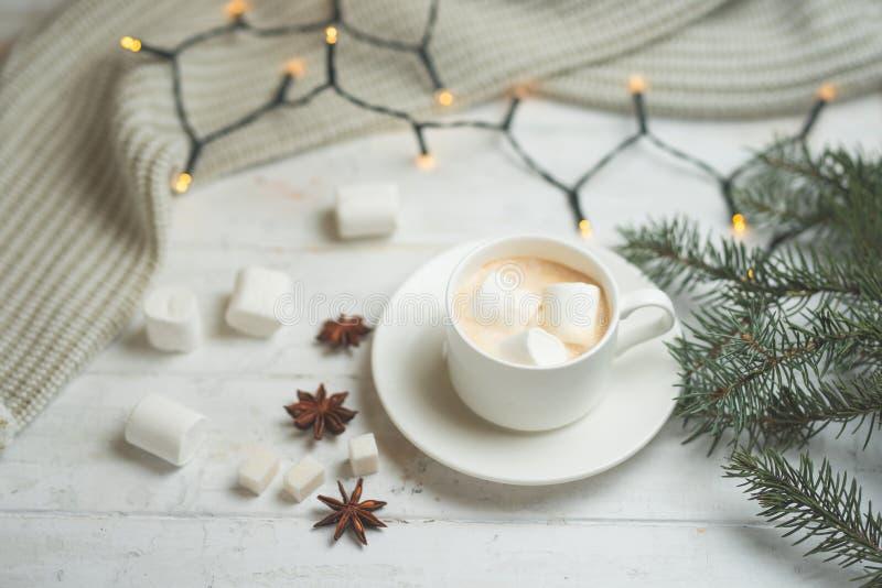 Кофе с молоком, latte с ручками циннамона и звездами анисовки с белыми шоколадом и зефиром, с ветвью рождества стоковые изображения