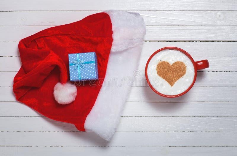 Кофе с символом формы сердца и подарочная коробка на шляпе Санта Клауса стоковое изображение rf