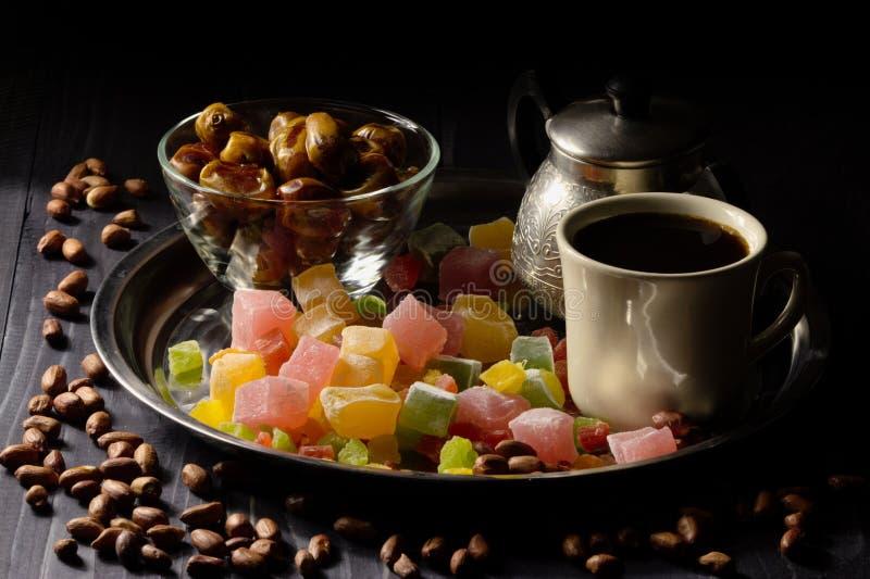 Кофе с турецким наслаждением, candied плодоовощами, pinuts и датами на предпосылке darck стоковые изображения rf