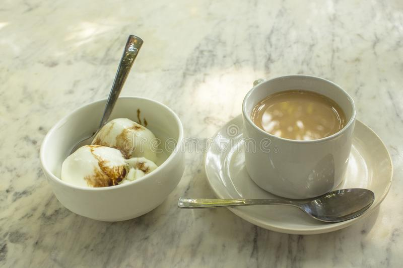 Кофе с шариками молока и мороженого в белых чашках с ложками на мраморном конце поверхности таблицы вверх стоковая фотография