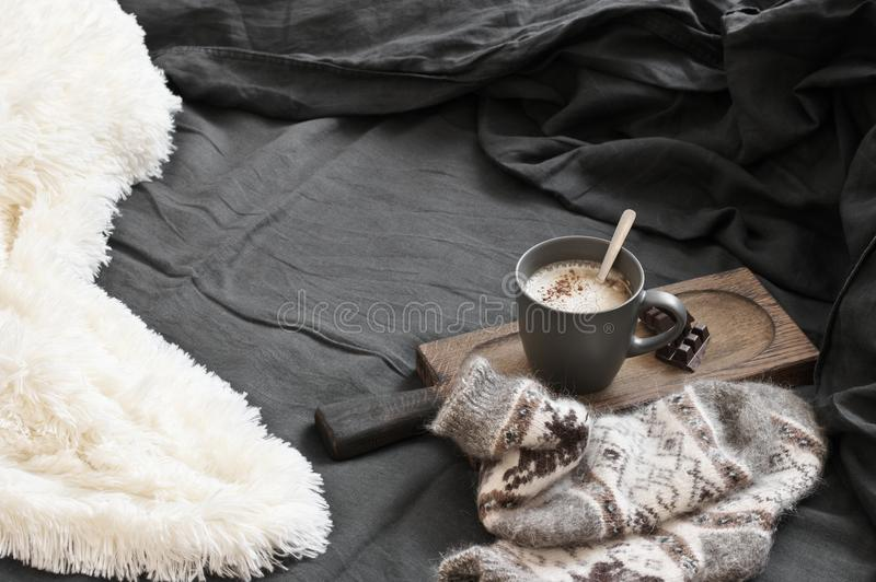 Кофе с шоколадом, шерстяными носками и одеялом в отменятьой кровати стоковое фото