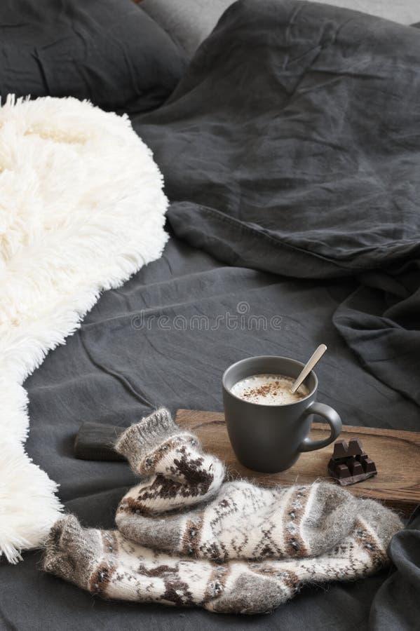 Кофе с шоколадом, шерстяными носками и одеялом в отменятьой кровати стоковые фото