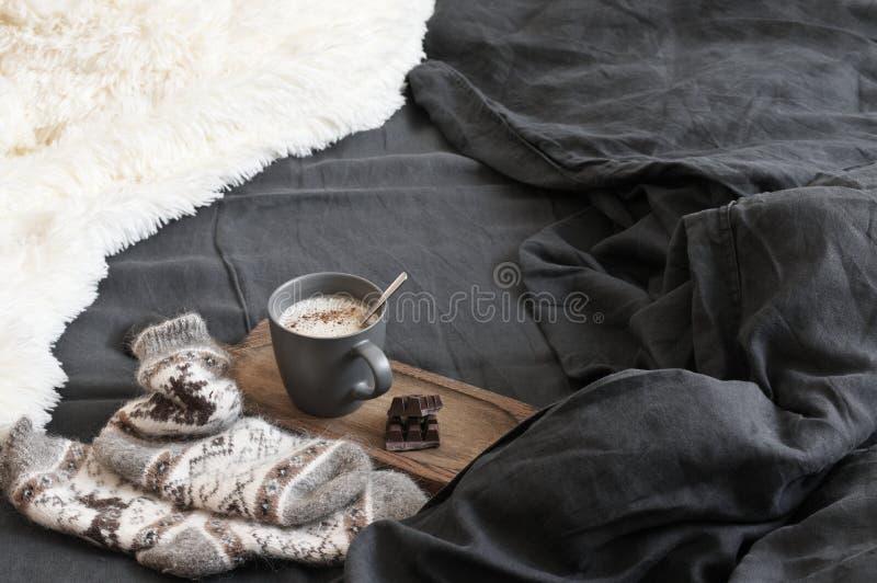 Кофе с шоколадом, шерстяными носками и одеялом в отменятьой кровати стоковые фотографии rf