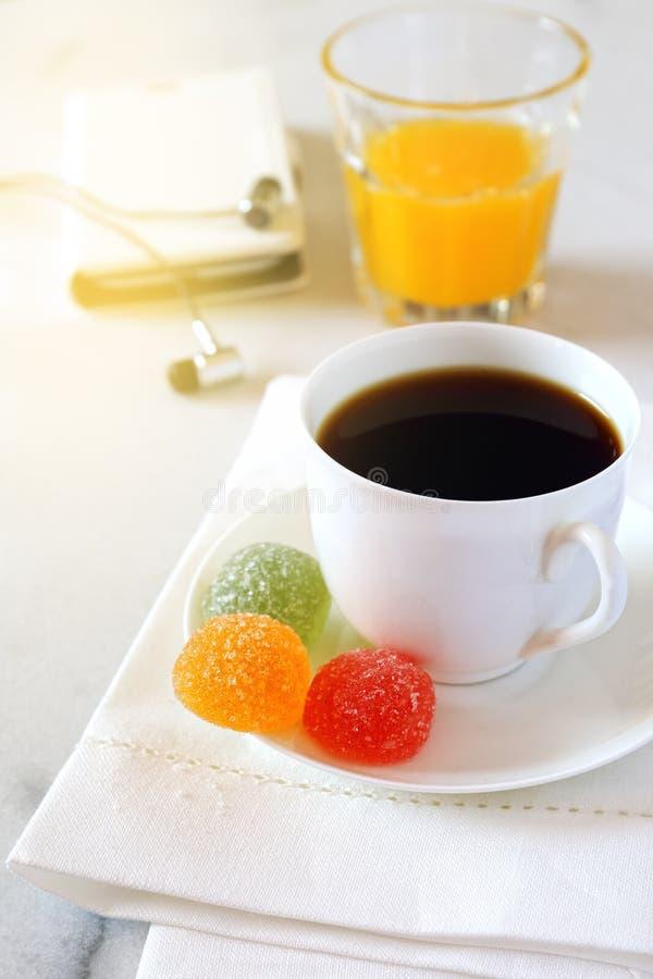Кофе утра, апельсиновый сок, конфета gummi и мобильный телефон стоковые фотографии rf