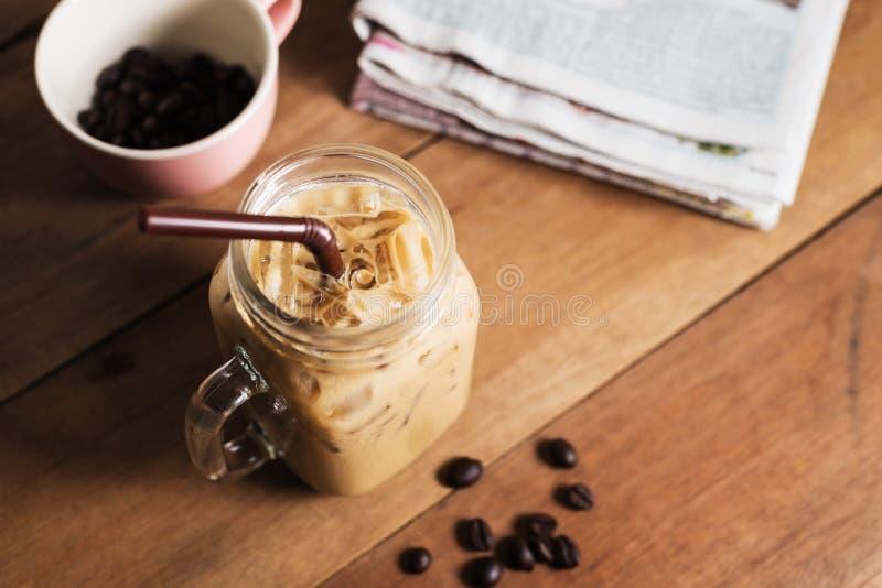 Кофе льда с молоком и газетой на таблице стоковые фотографии rf