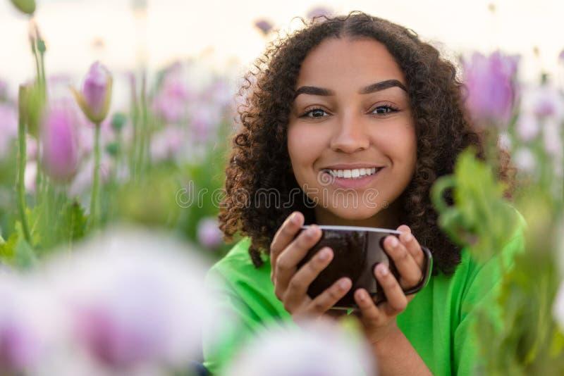 Кофе Biracial Афро-американской женщины подростка выпивая в цветках стоковые изображения