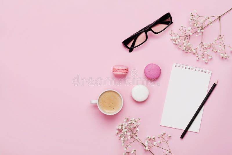 Кофе, macaron торта, тетрадь, eyeglasses и цветок на розовой таблице сверху Женский работая стол Уютное положение квартиры завтра стоковое фото rf