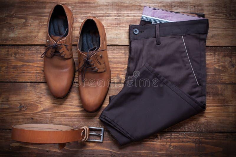 Коллаж одежды современных человеков на коричневой деревянной предпосылке стоковое фото