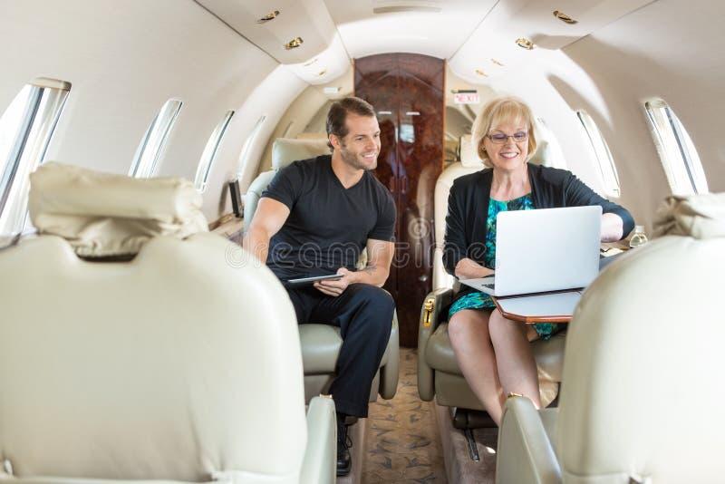 Коллеги дела обсуждая на частном самолете стоковые изображения