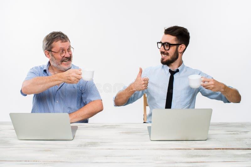 2 коллеги работая совместно на офисе на белой предпосылке стоковое изображение