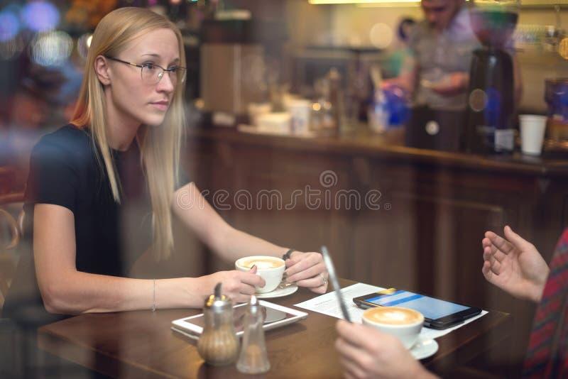 2 коллеги с таблетками обсуждая работу во время стоковое фото rf