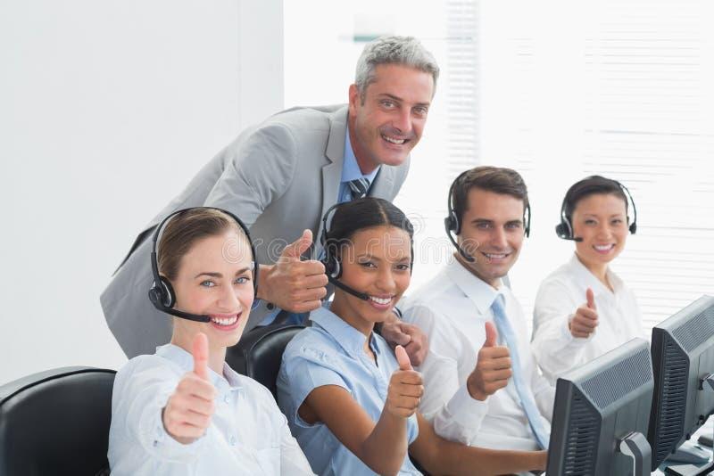 Коллеги с шлемофонами используя компьютеры пока показывающ жестами большие пальцы руки вверх стоковое изображение rf