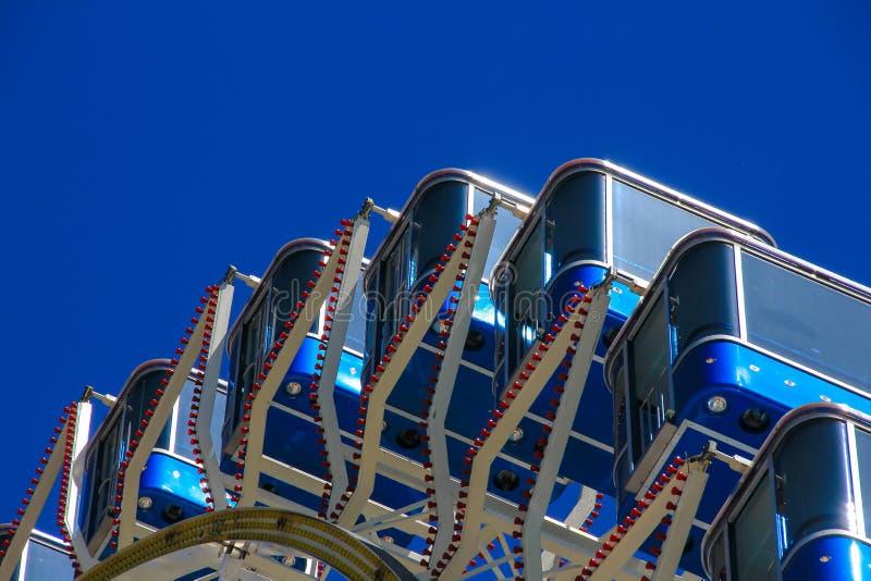 Колесо Ferris с голубыми кабинами на голубом небе стоковые изображения