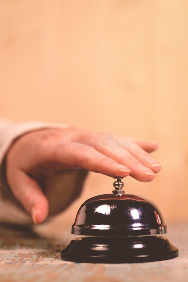 Колокол обслуживания гостиницы женщины звеня на приемной стоковые фото