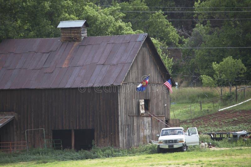 Колорадо и флаг США висят на амбаре с белым грузовым пикапом, Колорадо, США стоковая фотография rf