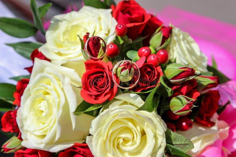 Кольца золота на розах wedding букет стоковые изображения