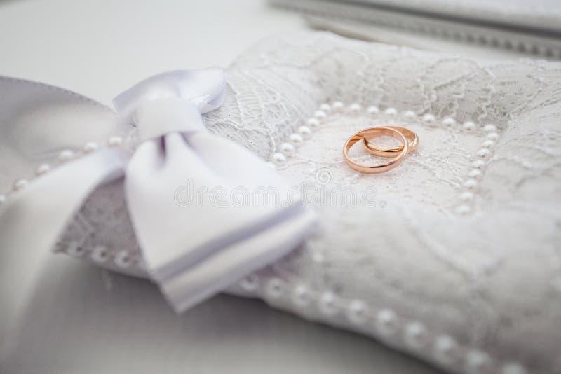 Кольца золота свадьбы на подушке стоковое изображение rf