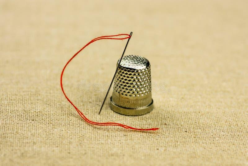 Кольцо и шить игла с потоком на linen ткани, концом вверх, теплый естественный тон стоковое фото