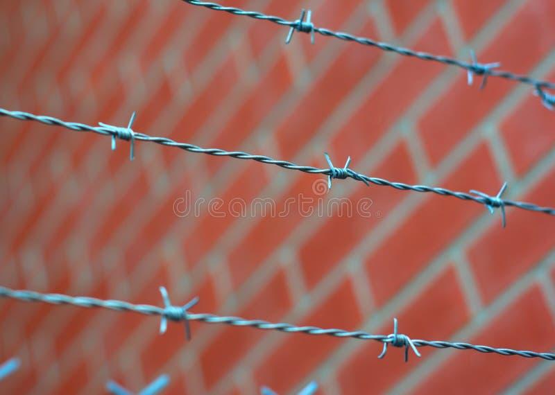 Колючая тюрьма загородки и красная кирпичная стена стоковое фото rf