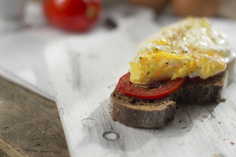 Краденное яйцо на тосте sourdough, с зажаренными томатами, грибами и листьями салата Здоровые, очень вкусные завтрак или завтрак- стоковые изображения