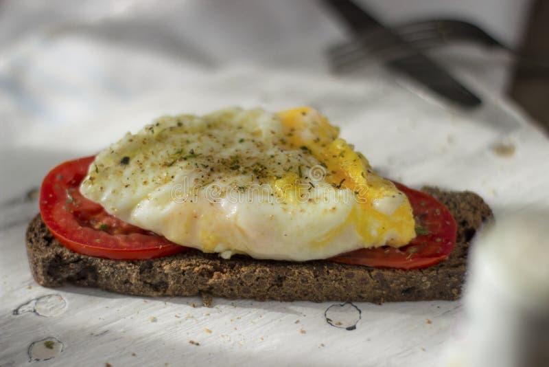 Краденное яйцо на тосте sourdough, с зажаренными томатами, грибами и листьями салата Здоровые, очень вкусные завтрак или завтрак- стоковое изображение rf