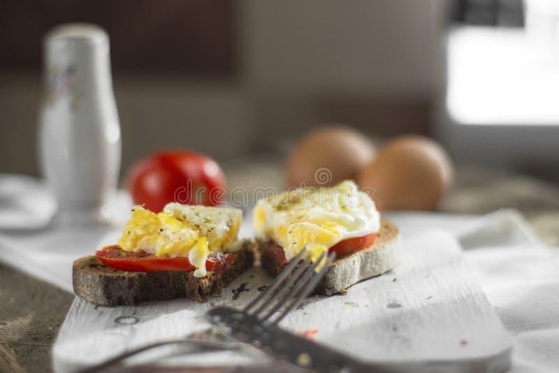 Краденное яйцо на тосте sourdough, с зажаренными томатами, грибами и листьями салата Здоровые, очень вкусные завтрак или завтрак- стоковая фотография rf