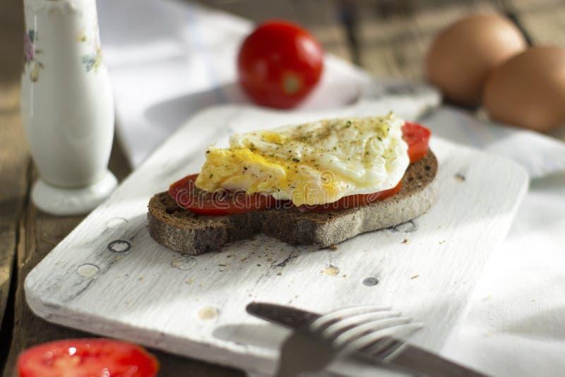 Краденное яйцо на тосте sourdough, с зажаренными томатами Здоровые, очень вкусные завтрак или завтрак-обед стоковое изображение rf