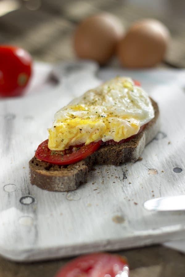 Краденное яйцо на тосте sourdough, с зажаренными томатами Здоровые, очень вкусные завтрак или завтрак-обед стоковые изображения rf