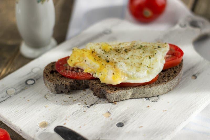 Краденное яйцо на тосте sourdough, с зажаренными томатами Здоровые, очень вкусные завтрак или завтрак-обед стоковые фото