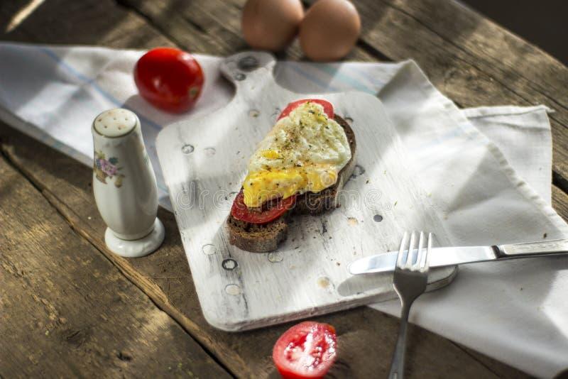 Краденное яйцо на тосте sourdough, с зажаренными томатами Здоровые, очень вкусные завтрак или завтрак-обед стоковые фотографии rf