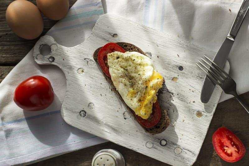 Краденное яйцо на тосте sourdough, с зажаренными томатами Здоровые, очень вкусные завтрак или завтрак-обед стоковое фото