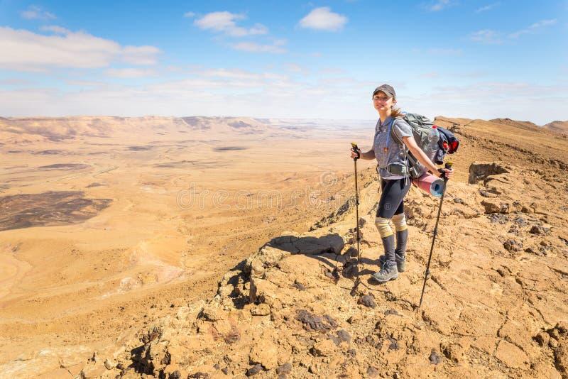 Край горы пустыни счастливого жизнерадостного туристского backpacker молодой женщины стоящий стоковые фото