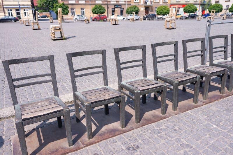 КРАКОВ, ПОЛЬША - ИЮНЬ 2017: Объекты искусства со стульями утюга на улице булыжника раскрытой в памяти об еврейском гетто Краков с стоковые изображения rf